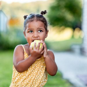 Portrait of a cute little mixed race girl in a yellow summer rummper eating an apple.